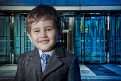 Modern child dressed businessman with hands in his tie and skysc Stock Photo