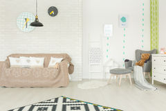 Modern child room with couch. Modern child room with white brick wall, couch, armchair, dresser Stock Images