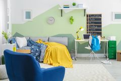 Modern child room interior with comfortable armchair. And bed Royalty Free Stock Image
