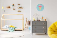 Modern child`s room interior. Grey cabinet against white wall with poster in modern child`s room interior with wooden bed stock images