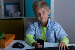 Modern child using phone and computer Royalty Free Stock Image