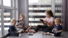 Modern childhood concept. 4 kids sit together with phones and tablets on the floor in house with panoramic windows stock footage