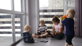 Modern childhood concept. 4 kids sit together with phones and tablets on the floor in house with panoramic windows stock video