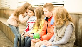 Children on a bench playing Chinese whispers Royalty Free Stock Photos