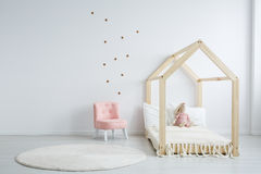 Modern children`s furniture in bedroom. Modern children`s furniture in a spacious bedroom with star stickers on the white wall, and a pastel pink comfortable stock images
