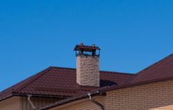 Modern chimney on the roof of the mansion in the sunlight. Clear blue sky background stock images