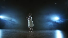 Modern choreography ballerina dancing on stage in the spotlight in slow motion. Dance musical show. Dramatic scene in