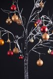 Winter Christmas tree. Modern Christmas tree with bare snow covered branches, decorated with hanging glitter balls, all on a black background Royalty Free Stock Photography