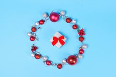 Modern Christmas wreath and giftbox on blue background. Christmas wreath made of silver ribbon, vibrant red and silver baubles on blue pastel background and stock images