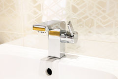 Modern chrome faucet in bathroom Royalty Free Stock Image