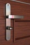 Modern chrome metallic door handle. On wooden door Royalty Free Stock Photo