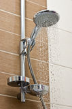 Modern chrome shower head. Closeup of a shower head with sprinkling water, massaging stream royalty free stock images