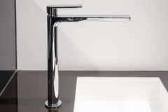 Modern chrome tall faucet. On black and white wash basin Stock Image