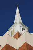 Modern church steeple. Low angle view of modern church steeple with religious cross, blue sky background Royalty Free Stock Photography