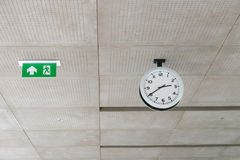 Modern circle clock and Exit sign hang on ceiling under building Stock Image