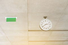 Modern circle clock and Exit sign hang on ceiling under building Stock Photos