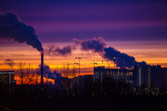 Modern city in the evening at sunset. Smoke comes out of the pip Royalty Free Stock Photos