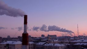 Modern city in the evening at sunset. Smoke comes out of the pipes. stock video