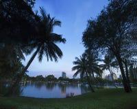 Modern city in a green environment at twilight, Suan Lum, Bangkok, Thailand. Royalty Free Stock Photo