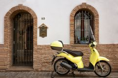 Modern yellow city scooter. Modern city scooter , parked in front of a rustic design house Royalty Free Stock Images