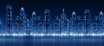 Modern city skyline at night with illuminated skyscrapers