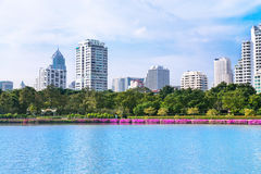 Modern city skyline of living district near park and lake Royalty Free Stock Image