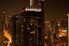 Modern city skyline at night. View of Dubai city skyline at dusk with skyscrapers in the foreground and streak of light caused by vehicles Stock Images