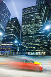 Modern city skyscrapers and fast motion trail car. Modern urban night scene with skyscrapers and a taxi car along the road with colored motion trail. Location stock photos