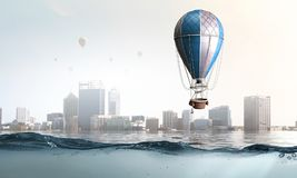 Modern city under the sea. Mixed media. Color aerostat flying above sunken city. Mixed media Royalty Free Stock Image
