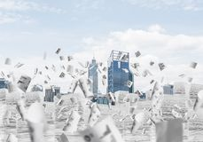 Modern city view with skyscrapers. Horizontal shot of flying papers and piles of documents with cityscape on background. Mixed media stock photography