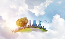 Concept of eco green life as elegant business center on white clouds. Modern cityscape with buildings and skyscrapers floating on clouds in sky Royalty Free Stock Images