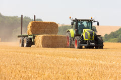 Modern Claas tractor collecting bales of straw Royalty Free Stock Photo