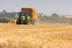 Modern Claas tractor collecting bales of straw Stock Photography