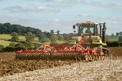 Modern claas tractor cultivating field Stock Photo