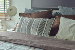 Modern classic style deep brown, gray and white bedding and reading lamp Stock Photography