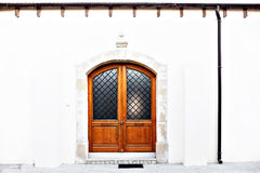 Modern classic wooden door. With 2 wings, glass. Mediterranean Europe style. White walls with black pipe. Stone entry stock image