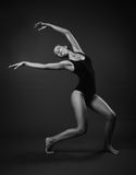 Modern classical dance theme: beautiful girl dancing sensual dance in a studio on a gray background, black and white photo Royalty Free Stock Photography