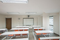 Modern classroom. A gleaming white classroom photographed from the back of the room. There are three rows of white desks that seat two people each. There is a Royalty Free Stock Photography