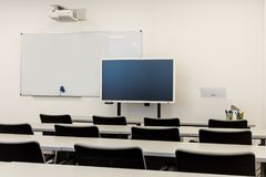Modern classroom interior, with white board, work desks and chairs Stock Image
