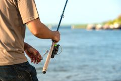 Modern clean fishing rod in hands Stock Images
