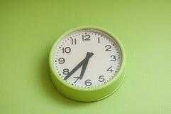 modern clock on green wall Royalty Free Stock Photo