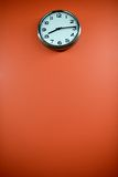 Modern clock on an orange background Royalty Free Stock Photo