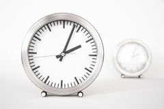 Modern clocks with metal frame in front of white Royalty Free Stock Images