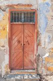 Modern closed dark red wooden door on yellow cement textured house. Wall Stock Photo