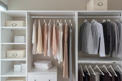Modern closet with clothes. Hanging on rail, white wooden wardrobe, interior design concept royalty free stock images