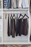 Modern closet with row of pants hanging in wardrobe Royalty Free Stock Image