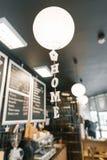 Modern coffee shop, inre, stångräknare, fokus på den vita runda papperslampan och ordhemmet i träbokstäver Hem- kafébegrepp arkivbild