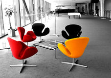 Modern colorful chairs. Colorful modern chairs in a lounge with black and white background stock photos