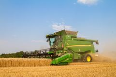 Modern combine harvester cutting crops corn wheat barley working golden field Royalty Free Stock Photo