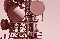 Modern Communication Tower. Close up details of many different kinds and shapes of antenna and transmitting/receiving units on a large, modern, commercial Royalty Free Stock Image